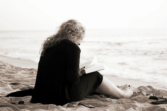 海で読書をする女性